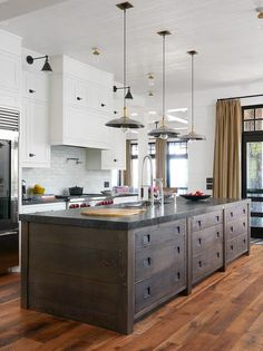A white plank ceiling is dotted with three vintage galvanized barn pendants illuminating a dark brown salvaged wood kitchen island fitted with stacked drawers topped with honed black marble framing a stainless steel dual sink and stainless steel pull-out faucet.