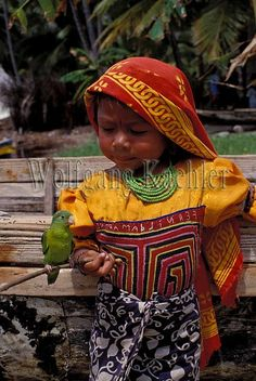 Panama, san blas islands, acuatupu island, kuna indian girl with pet parrot