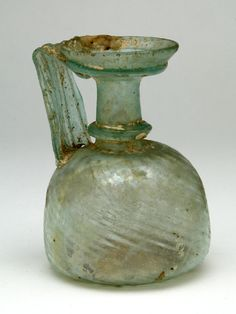 "Juglet in Aqua Glass. Roman Syria, 3rd to 4th century AD. Cf. G.F.M. fig. 102b; Newark, fig. 117. Height: 4-3/8"". $288"