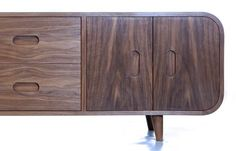 1950's inspired low sideboard. Veneering the cabinet in one piece is the biggest challenge of the design and having tried and failed with all modern techniques it was finally accomplished using the oldest of methods, that of using hide, glue and hand hammering the veneer. American Black Walnut outside with Canadian Hard Maple interior.  DESIGN ID:SA1 PRICE:£3500 (VAT not applicable) MATERIALS:Walnut DIMENSIONS:H 50cm x W 150cm x D 40cm