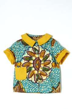 African turquoise print shirt with mustard collar and turn up sleeve detail. An ethnic print boy's summer shirt leading the way in contrast pattern clothes for kids. A new style of summer shirt for What Mother Made. The rounder collar and contrast turn-up sleeve takes a step back to the 50's. You can wear this shirt casually with shorts or for smarter occasions with a dungaree or smart trouser. Match the shirt with the self brace shorts for a truly vintage inspired look