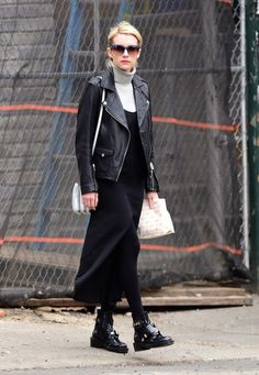 Emma Roberts layers a black leather jacket over a chunky turtleneck, a black midi-dress and black patent booties.