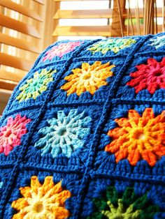Crocheted flowers framed in blue to make a pillow cover