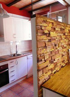 Cocina independiente, del salón con un muro  de piedra y cristal.