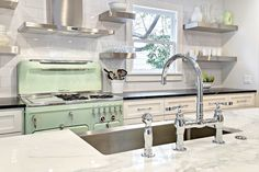 Stunning+kitchen+with+white+shaker+cabinets+accented+with+Restoration+Hardware+Asbury+pulls+alongside+black+perimeter+counters+which+frame+a+mint+green+stove+with+stainless+steel+stove+hood+highlighted+by+a+oversizes+white+subway+tiled+backsplash+and+stacked,+floating,+stainless+steel+shelves+in+place+of+upper+cabinets.