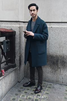 London Collections Men street style, an oversized coat with a two-tone knit jumper and slim black jeans, finished off with a pair of high shine smart shoes | The Idle Man