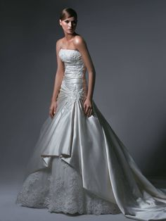 Blue by Enzoani Ankara Satin and taffetta ivory A-line wedding gown, with embellishments on the bodice and train. This gown has a beautiful vintage tulle and lace edged hem at the front of the skirts. Pearl beads and appliqued floral patterns adorn the gown on the bodice and the cathedral length train. Size 10 RRP £1,350 Sale Price £795 Professionally dry cleaned Can be viewed at our boutique in Petersfield, Hampshire.