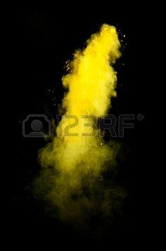 Freeze motion of yellow dust explosion isolated on black background Stock Photo