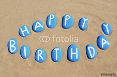 Happy Birthday on blue stones over the sand