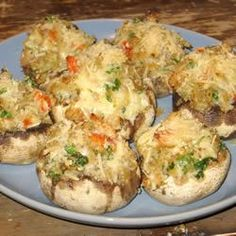 Crab and Lobster Stuffed Portabella Mushrooms 3/4 cup melted butter, divided 1 pound fresh mushrooms, stems removed 1 cup crushed seasoned croutons 1 cup shredded mozzarella cheese  1 (6 ounce) can crabmeat, drained 1 pound lobster tail, cleaned and chopped 3 tablespoons minced garlic 1/4 cup shredded mozzarella cheese (optional)