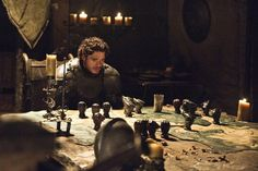 Game of Thrones- Richard Madden as young Lord Robb Stark, the King of the North. This photo is in comparison to the pic i just posted w/Renly Baratheon in his chambers surrounded  by his family's wealth...here, you have Robb heading up an army on the move, is his tent can see a map of the Kingdom w/various silver figures representing different Families It's a much harder, colder, more barren can you imagine how cold they must've been back then?!?