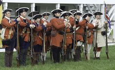 Reenactors representing the French and Indian War (Seven Years War) garrison of Fort Frederick fix their bayonets to their muskets before raising the fort's flag.