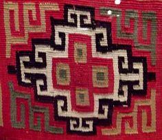 """Detalle de un """"uncu"""", una pieza textil inca, donde puede verse representada una chakana o cruz andina. El objeto pertenece a la colección de objetos arqueológicos peruanos del Museo de América, Madrid, España. Se cree que el uncu data de principios de la época colonial peruana."""