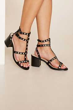 A pair of faux leather sandals with a strappy design, high-polish studs throughout, double buckled ankle straps, and a block heel.