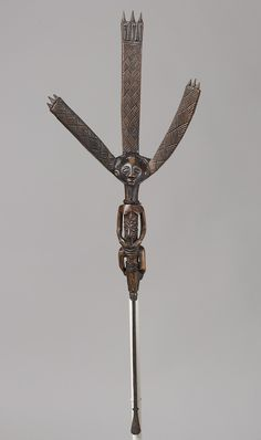 Bow Stand with Female Figure, 19th–20th century Democratic Republic of Congo; Luba Wood, metal, beads, string   This elegant bow stand was one of several royal sculptures owned by a Luba monarch. Such artifacts make a reference to the Luba culture hero Mbidi Kiluwe, a foreign prince who ushered in an era of enlightened leadership and founded a dynasty of sacred Luba kingship.