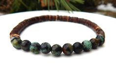 Popular mens bracelet made with 6mm African Turquoise surrounded by coco wood. Very cool. African Turquoise Properties: Helps one to express themselves with more clarity. Often know as a grounding sto