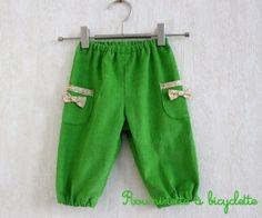Pantalon bébé petits noeuds en velours vert pomme bordé de liberty Eve vert et jaune.