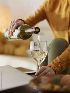 Crop woman pouring white wine by Milles Studio for Stocksy United. Faceless shot of elegant woman pouring white wine in glass chilling alone at home.