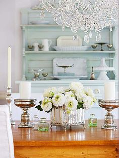 Front and Center -An old painted buffet, antique silver candleholders, and serving pieces combine with glass bottles to create a country glam dining room. Scour salvage yards and flea markets to find gorgeous silver pieces that need a new home. Use silver polish to make them shine or keep them as is to preserve the worn look.