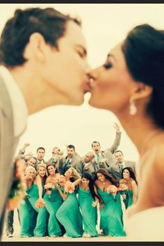 bride & groom kissing with wedding party in the back