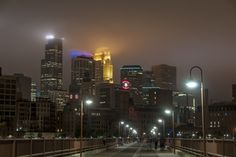 https://flic.kr/p/HWXMvN | Minneapolis Haze | Low clouds obscure the tops of the IDS Center, Wells Fargo Center and Capella Tower in Minneapolis at the end of a warm, humid June day while people go about their business on the Stone Arch Bridge.
