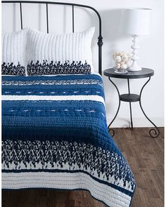 dark wood floors, white walls, wrought iron bed and bed stand, white/blue/black quilt and pillow shams