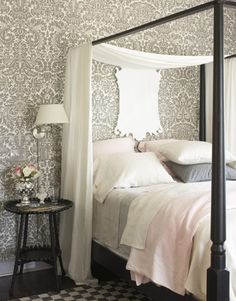 Bedroom with white and grey patterned wallpaper and white sheets with black canopy bed