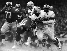 American football player John Henry Johnson (center, #35) of the Pittsburgh Steelers runs with the ball during a game against the New York Giants, early 1960s (between 1963 and 1965).