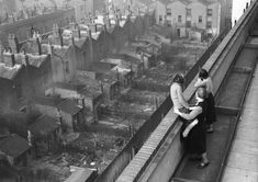 This picture from 1938 shows a woman and her two daughters, who have just moved in to Hillcott House, then a brand new block of council flats in Shoreditch, looking at the surrounding old terraced housing (Photo by London Express/Getty Images) Vintage London, Old London, East End London, North London, London History, British History, Asian History, Tudor History, American History
