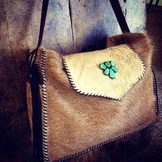 The Buckaroo Diaper Tote in all tan cowhide with a vintage jade shoe clip on the flap. gowestdesigns.us