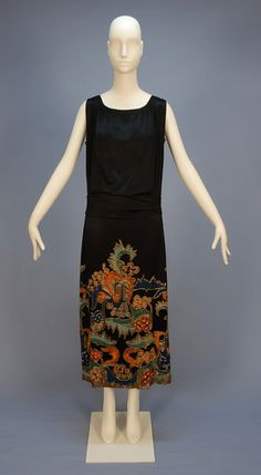 """Embroidered and beaded black silk charmeuse evening dress (front), by Doeuillet, French, c. 1920's. Sleeveless black silk charmeuse heavily embroidered in vibrant shades of orange, aqua, blue, pink and yellow with gold bugle beads in an abstract floral on the upper back and over-skirt front and sides, self sash having back loop and drape, cream silk under dress having applied lace to the sides. Label: """"Doeuillet Paris Londres"""""""
