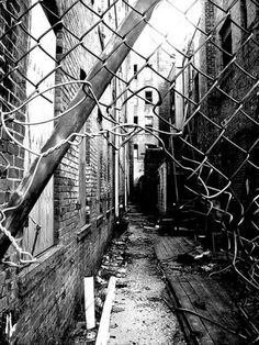 Urban Decay: Broken wire fence, leading on to an alleyway with pieces of wood and rubbish lying around. This image is in black and white which gives a darker, dull atmosphere.