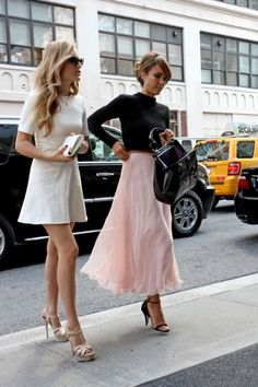 Jessica Alba in black heels, a black crop-top turtleneck, and long light pink skirt, with a friend in a white dress and matching platform heels.