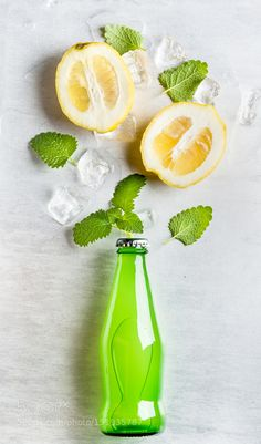 Pic: Green lemonade bottle with ingredients and ice cubes on steel background
