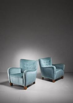 A pair of Danish lounge chairs with a blue, buttoned velvet upholstery. The chairs are a variation on model 1669 by Fritz Hansen.A wonderful and comfortable pair in an excellent condition.