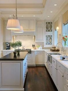 Kitchen White Cabinets and Counters with Dark Island Counter and Wood Floors. Lovely ceiling and door designs. by Wells & Fox Architectural Interiors. by earnestine