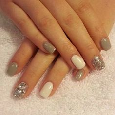 Taupe colored nails with a white accent nail & glitter.