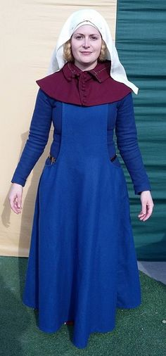 My surcoat, hand sewn in wool with waxed linen thread. Also showing my new purple liripipe hood, hand sewn in wool with waxed linen thread. Late 14th century.