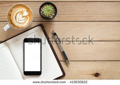 Office desk with blank screen smartphone,pen,notebook and coffee cup on  wood table.Top view with copy space.Office supplies and gadgets on…