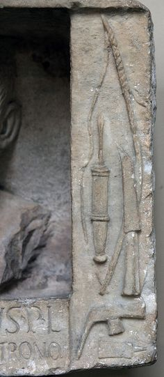 Detail from a Roman funerary relief found in the environs of Frascati, Italy. Now in the British Museum. The tools depicted are connected with woodworking: In the center a bow and the drill bit. A knife or heavy socketed chisel for cutting mortises, and, at the bottom, an adze-hammer and a paring chisel, tanged, without the handle. British Museum inv. 1954.12-14.1 (1954,1214.1). Dated by the museum to the late first century BCE.