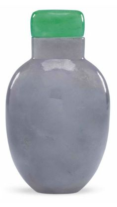 Lavender Jadeite snuff bottle, 1780-1880. The tapering ovoid bottle is carved from stone of pale mottled lavender color with a soft polish with a  jadeite stopper