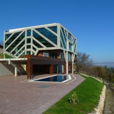 This Conservatory House in Bulgaria by Ignatov Architects was designed to host small music events and house a large flower conservatory. It was built on the site of an old sand quarry for neighboring villages, which was later turned into an eroded waste dump.  The home fits into an existing quarry pit, providing a compact structure that fills the void without obstructing on the natural surroundings...
