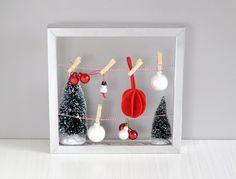 Hang een waslijntje in een leeg fotolijstje en maak er een kersttafereeltje van! Bijvoorbeeld met foto's of kleine kerstdecoraties. Meer foto's & ideetjes op www.christmaholic.nl.