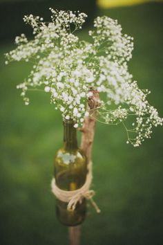 Natural Stick Suspended Wine Bottles, tied with twine, filled with petite flowers.  Maybe lining walk to ceremony?