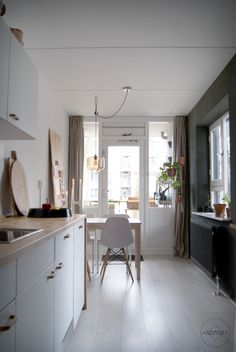 Look inside in a appartment in Amsterdam. Kitchen with diner table and lot's of light. Use of contrast colors white and dark green and natural materials like wood and linnen.  Read the blog at: http://www.pure-original.nl/blog?Binnenkijker-in-een-groen-appartement-in-Amsterdam  Photography by Ayame styling & design by Iris Floor   www.irisfloor.nl