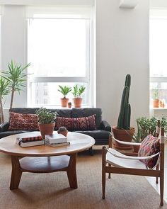 Sofa, chair, coffee table set up could be cool for client meetings  Danish safari chair, round coffee table, plants, sisal rug / office of Refinery29 in Cooper Square, Manhattan, designed by Chad McPhail / photo by Ingalls Photography