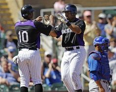 Colorado Rockies' Wilin Rosario, center, is met at the plate by teammate Chris Nelson, left, after hitting a two-run home run