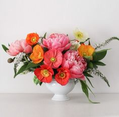 Bright, clean and happy centerpiece of pink peonies, coral, orange, and white poppies, with veronica in a white footed vessel. | Ellamah Floral Design