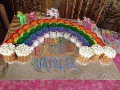 Rainbow Cupcakes I made for my daughters my little pony birthday party. Rainbow are all cupcakes and the clouds are mini bundt cakes.