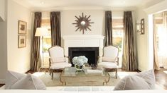 Ashley Goforth    white & taupe modern french living room design with with taupe gray silk drapes, bronze sunburst mirror, white fireplace, white & gray bergere chairs, brass & glass coffee table, floor lamp and greige walls paint color.